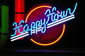 "A neon ""Happy Hour"" sign implying how to cut the cost of living in New York when going out to have fun"