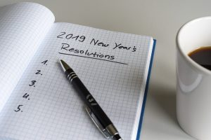 a notebook with New years resolutions and a pen