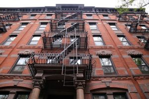 red-brick NYC building with a fire escape
