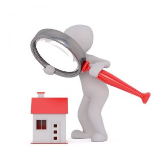 a male model holding a magnifying glass over a house model
