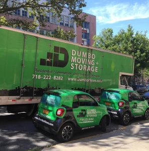 a green moving truck and two green cars with a dumbo moving and storage logo