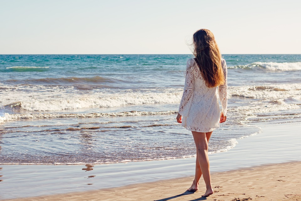 a girl in a white dress looking at the ocean