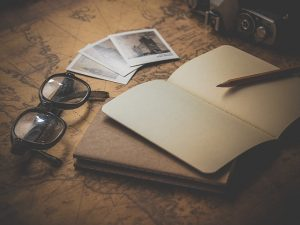 Vintage picture of a notebook, glasses, pen and photos - the best time for relocation isn't when you are down
