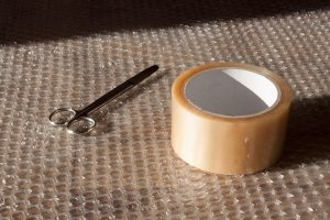 bubble wrap, scissors and tape to use to pack fine china for storage