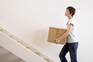 Woman carrying moving box up stairs
