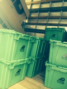 a pile of stacked, green plastic moving bins with a ''dumbo moving and storage'' logo ready for an eco-friendly relocation