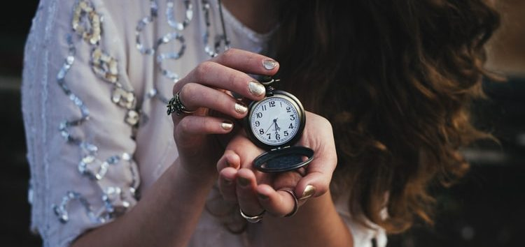 a girl holding a pocket watch