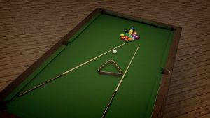 a green pool table with balls and two cues