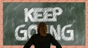 a girl looking at the board with the ''keep going'' writing
