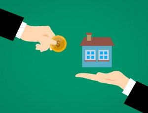 a hand holding a coin and real estate agent's hand holding a house model