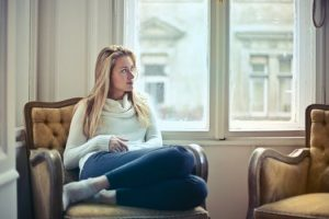 A blond woman sitting in the brown armchair by the window in her NYC home