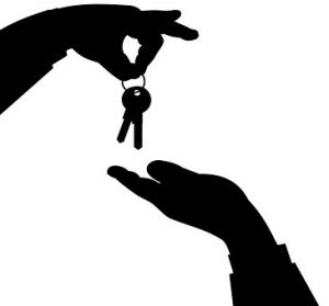 a landlord's hand giving keys to renters'hand