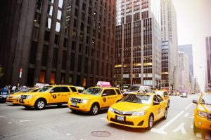 An overcrowded NYC street with a lot of yellow cabs and tall buildings