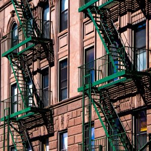 A red-brick building with a green fire escape is one of so many options when renting in NYC