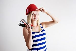 woman with a red helmet holding tools for upkeep works before selling a house