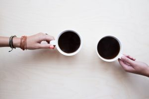two hands holding coffee cups on a white table
