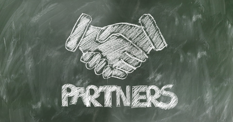 A blackboard with the word partners written on it and two hands.