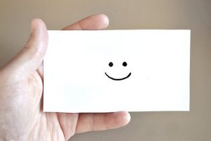 a hand holding a paper with a smiley as an indicator of positive moving reviews
