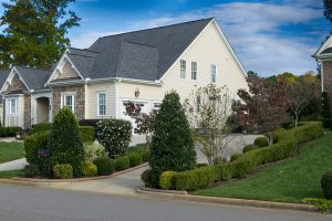 white suburban house with a large lawn and driveway