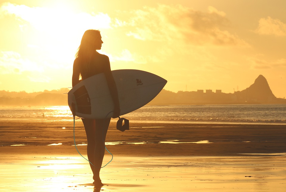 a girl with a surfboard on the beach after moving to a warmer climate