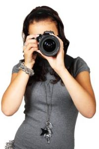 a girl in a grey shirt using a camera