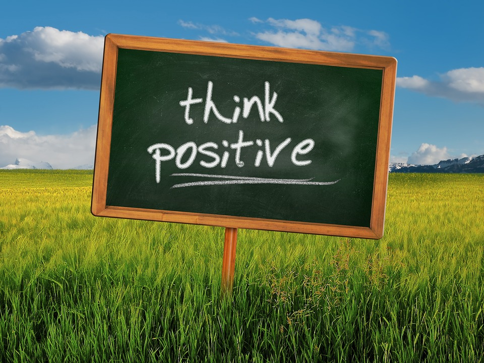 a green board stating think positive