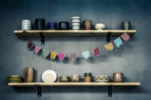 two wall shelves with ceramic bowls and glasses and a banner
