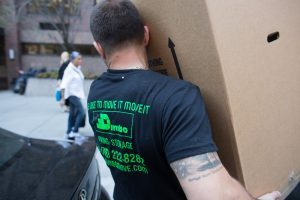 Dumbo mover in a black t-shirt with company's contact details carrying a cardboard box